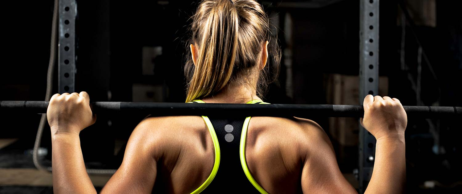 Woman's muscular back as she lifts weights.