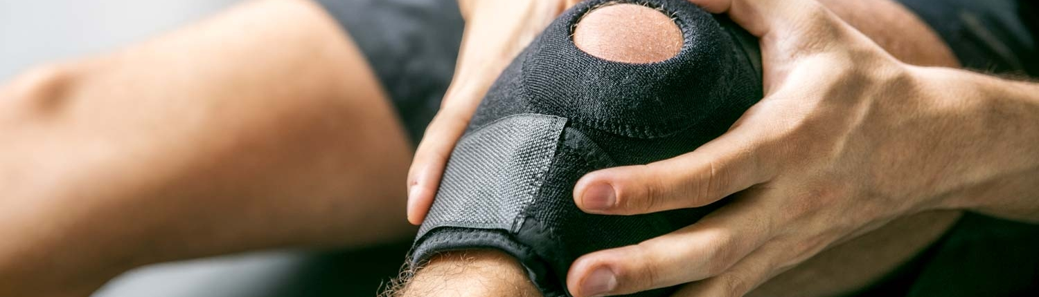 Close up of a man holding his knee in pain.