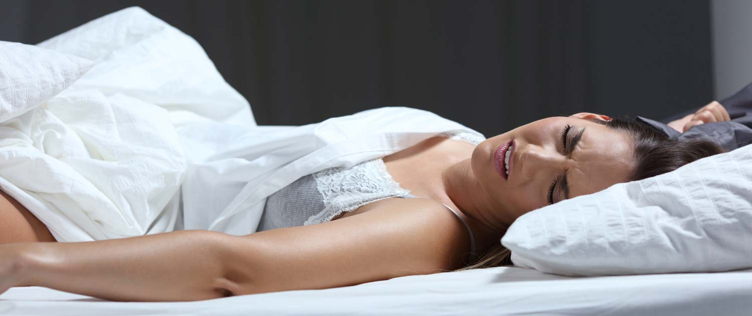 Woman in her bed unable to sleep due to restless legs.