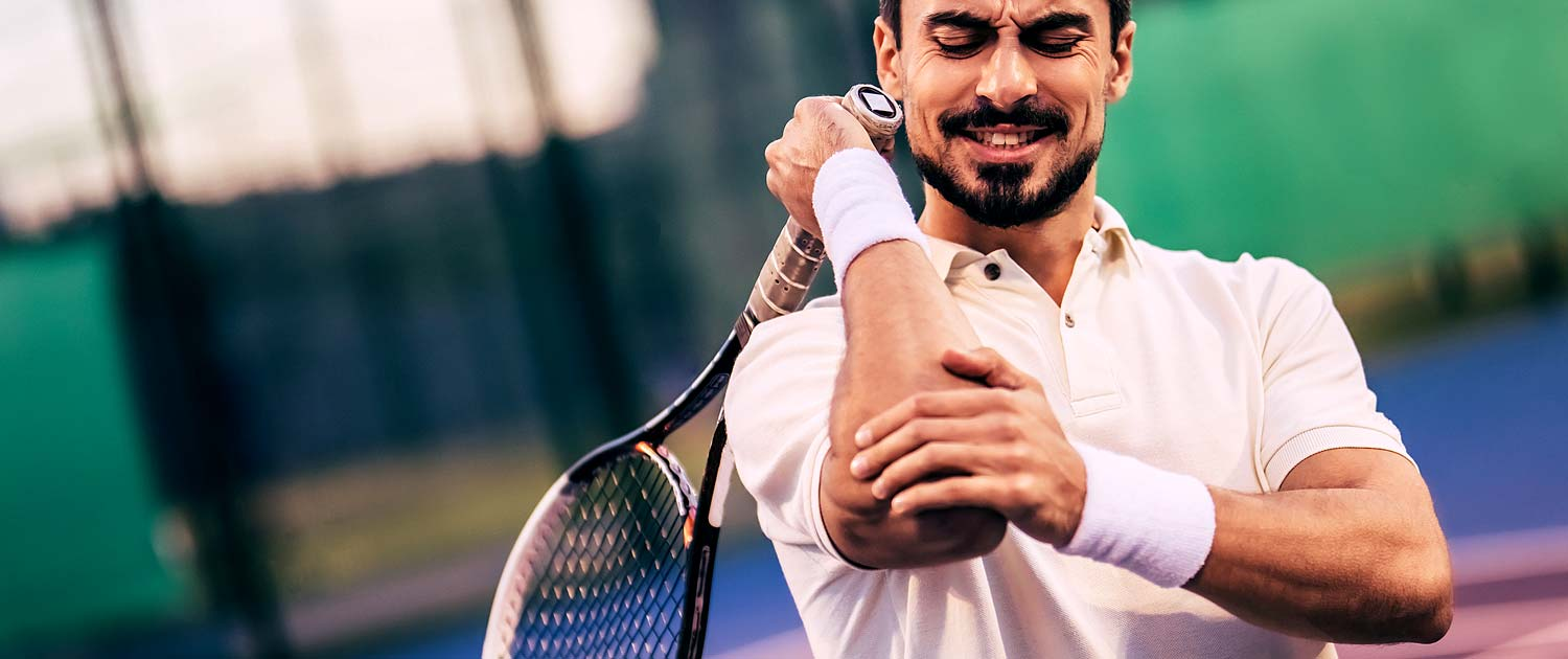 Tennis player holding his elbow in pain and grimacing.
